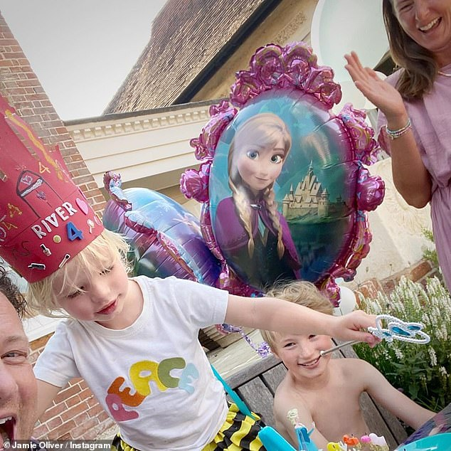 Family time: The celebrity chef, 45, shared a series of images to Instagram on Saturday surrounded by wife Jools, nine-year-old son Buddy as well as birthday boy River