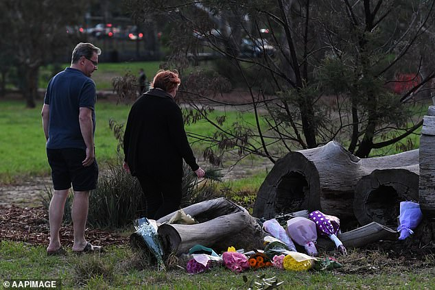 Mourners are seen laying flowers at a makeshift mural for Courtney Herron whose body was found in Royal Park, Melbourne, Sunday, May 26