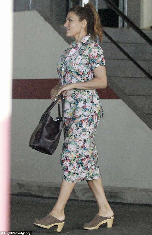 Springtime: Eva, 44, buttoned herself into a splashily colorful short-sleeved floral dress, knotting up the hem at the front to offer an extra glimpse of leg