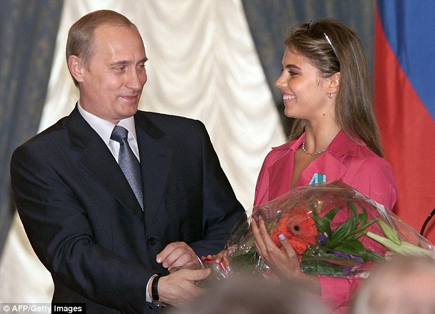 Putin hands flowers to his rumoured lover Kabaeva after he awarded her with an Order of Friendship  in the Kremlin on June 8 2001, in one of their very rare public appearances together