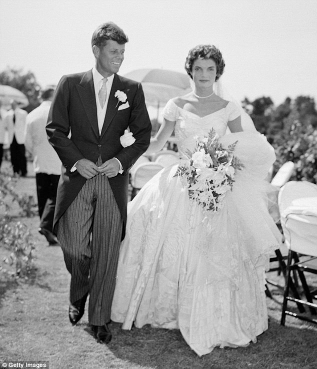 American royalty: John F. Kennedy is pictured walking alongside his bride Jacqueline Kennedy née Bouvier at their 1953 outdoor wedding reception in Newport, Rhode Island